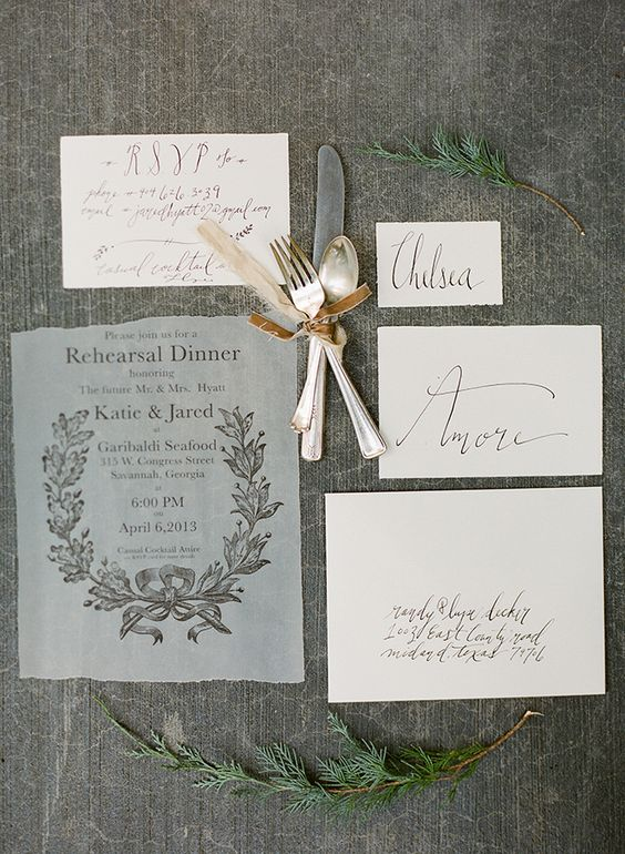 a semi sheer rehearsal dinner invitation with a raw edge and chic calligraphy and botanical prints for a refined event