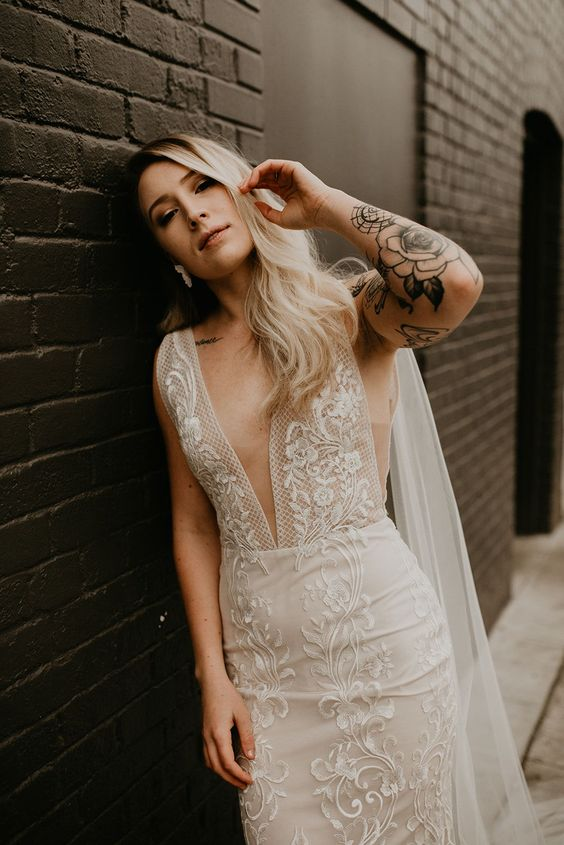 a sheath lace wedding dress with no sleeves and a plunging neckline plus tattoos that are shown off