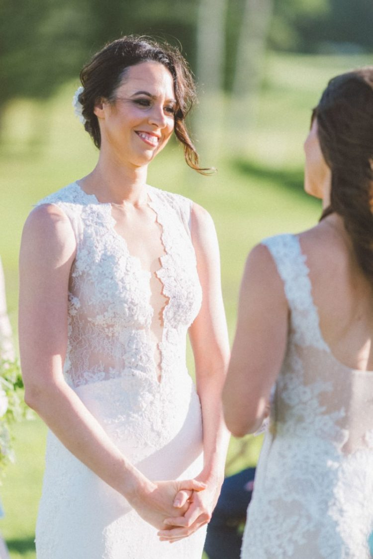 a sheath lace wedding dress with thick straps and a plunging neckline looks very sexy and cool