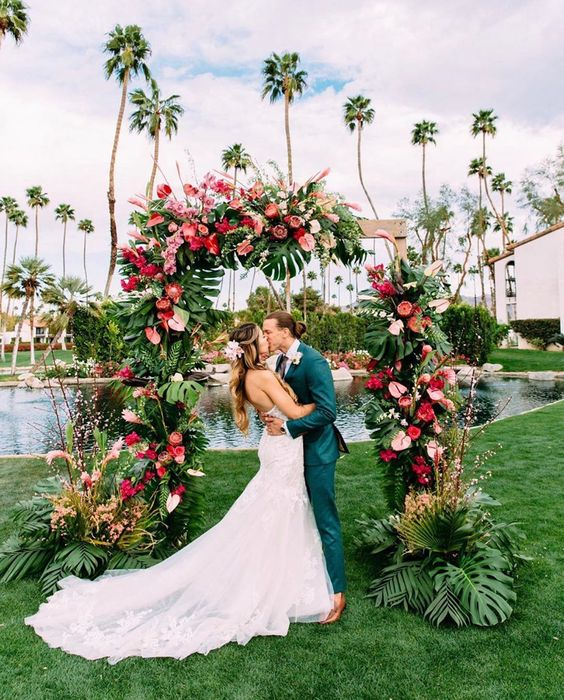 a spectacular wedding arch decorated with greenery and monstera leaves, pink, red and blush blooms and fronds