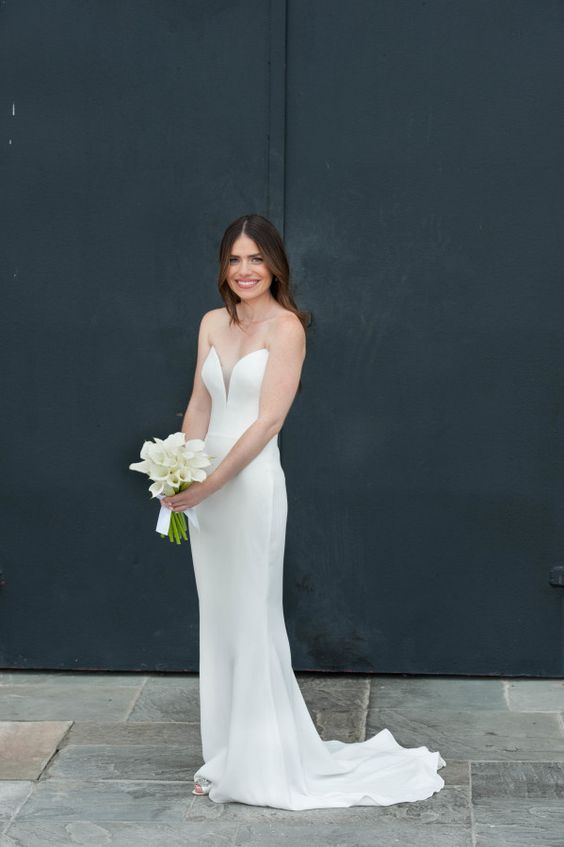 a strapless plain sheath wedding dress with a plunging neckline and a train is very elegant