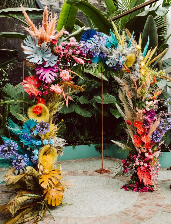 a super colorful tropical wedding arch done with spray painted fronds and leaves, grasses and blooms in all the colors of rainbow