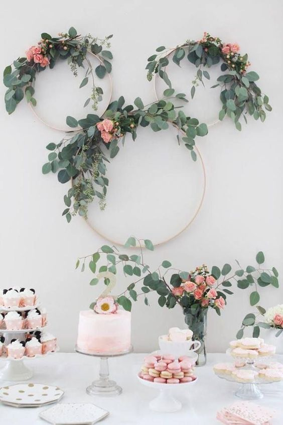 a sweets table with macarons, cupcakes, cookies and embroidery hoops with greenery and pink roses