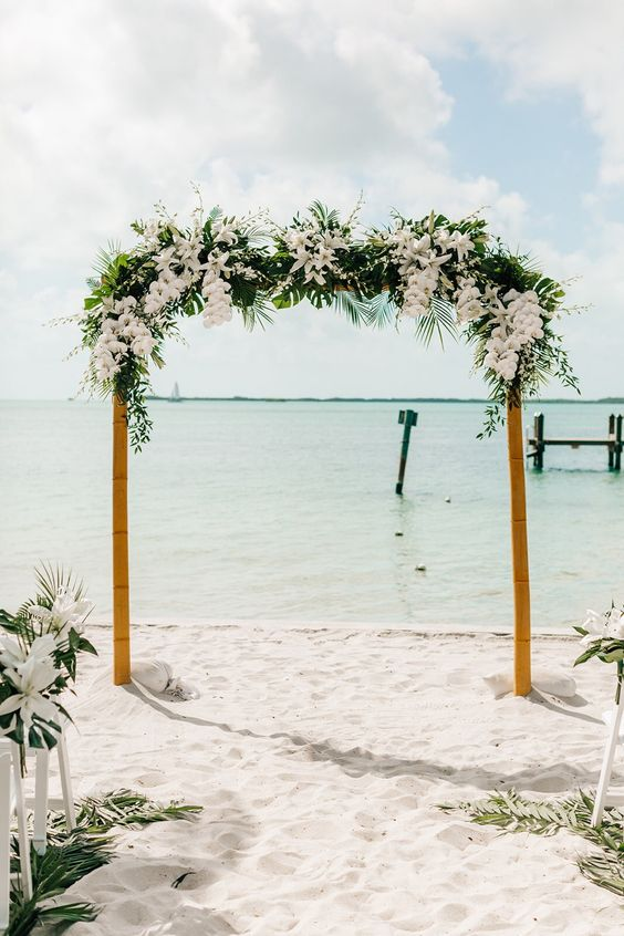 a tropical wedding arch covered with greenery and tropical leaves and white lilies and orchids is very refined