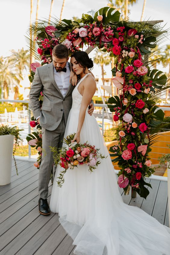 a tropical wedding arch decorated with tropical leaves, red, blush, orange and fuchsia blooms