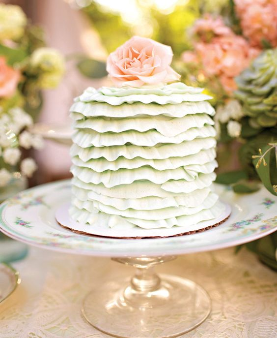 a vintage-inspired bridal shower cake in mint green with ruffles and a fresh bloom on top