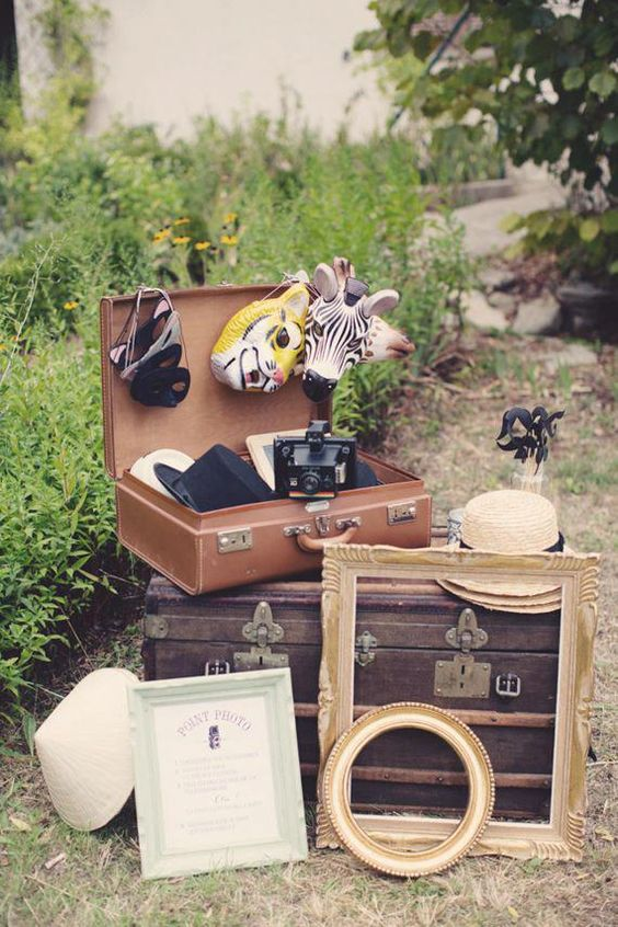 a vintage suitcase with various animal masks, vintage frames and vintage cameras for your wedding photo booth