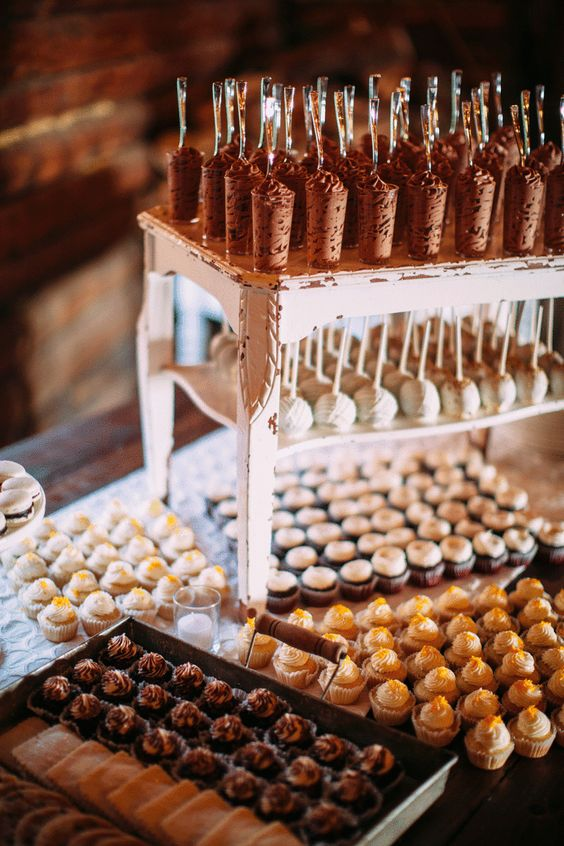 a vintage white stool used as a wedding dessert stand is a simple idea - just reuse what you already have