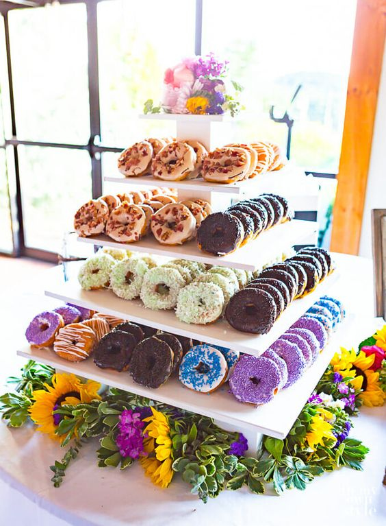 a white plywood tiered wedding stand with bright blooms, greenery and lots of donuts is always a good idea