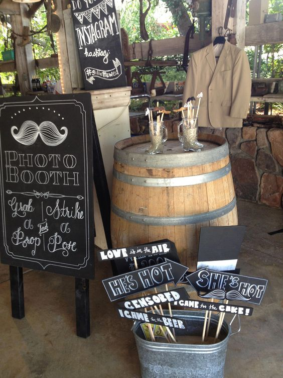 an arrangement of chalkboard props and a matching photo booth sign are great for a rustic or modern photo booth