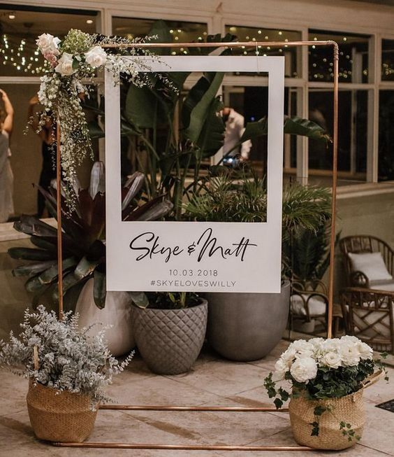 an elegant Polaroid photo booth with fresh blooms and greenery is a chic and stylish idea