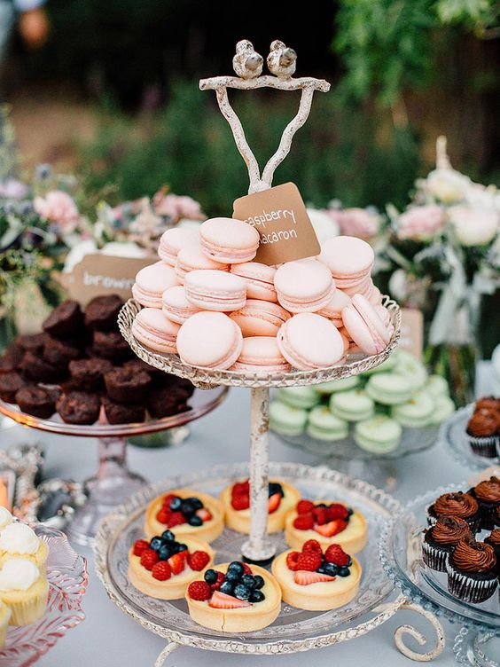 an elegant glass wedding dessert stand with cute birdies on top is a lovely idea for many weddings, from vintage to rustic ones
