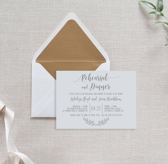an ethereal and neutral rehearsal dinner invitation with calligraphy and an envelope with gold lining