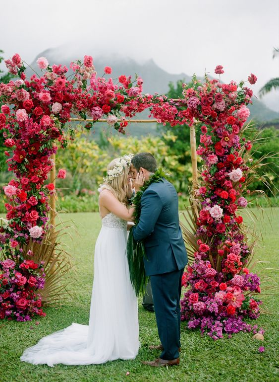 an extremely lusha nd colorful floral wedding arch covered with red, pink, purple blooms and some gilded leaves
