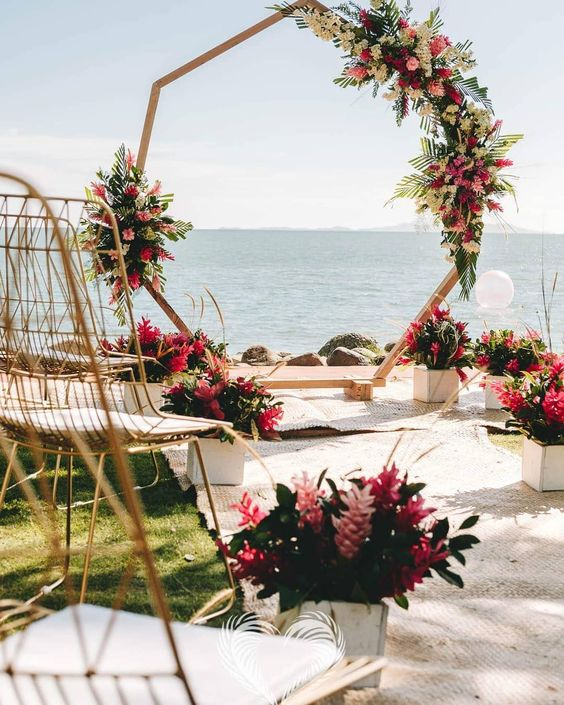 an octagon wedding arch decorated with greenery, white and pink flowers and matching arrangements lining up the aisle