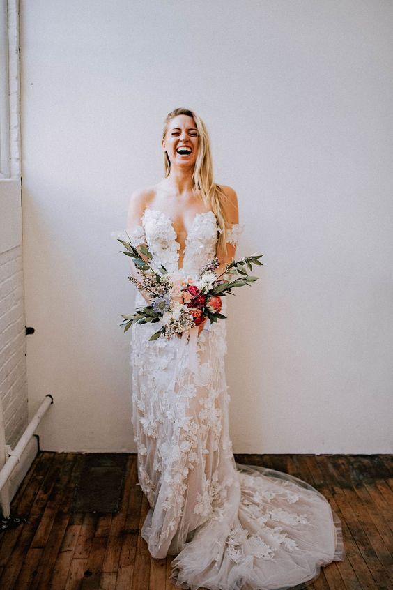 an off the shoulder lace applique wedding dress with a covered plunging neckline and a train