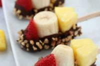banana, pineapple, strawberry kabobs with chocolate and nuts on top are deliciously fresh