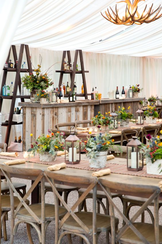 candle lanterns and colorful potted blooms for rehearsal dinner decor with a rustic feel