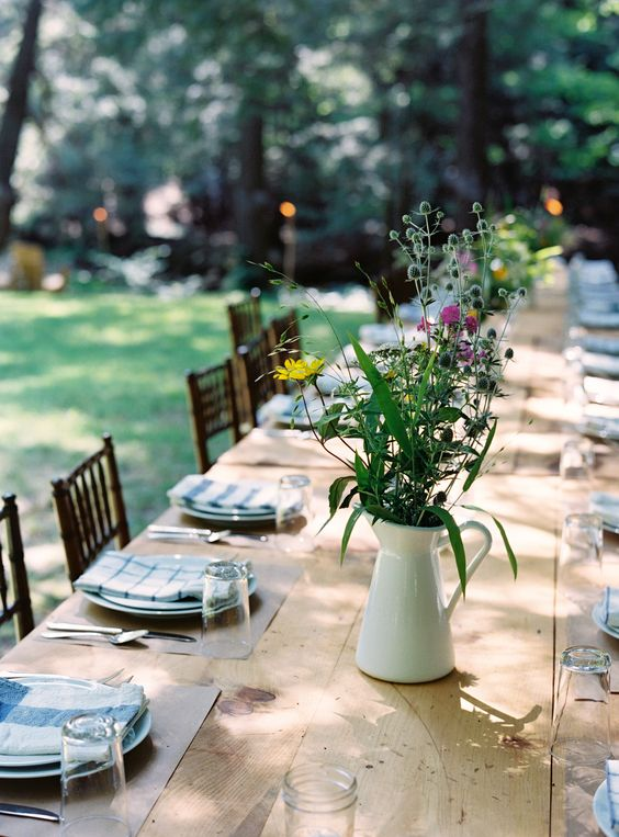 a backyard rehearsal dinner tablescape with neutral placemats, plaid napkins, bright wildflowers in a jug and simple silver
