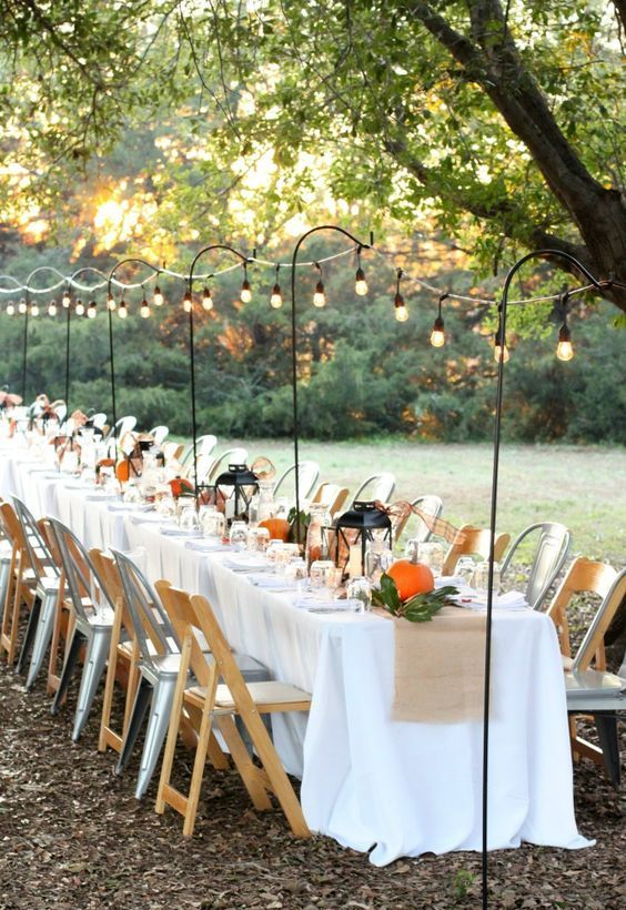 a bbq rehearsal dinner tablescape with candle lanterns, foliage and pumpkins, lights over the table