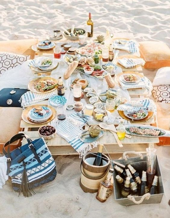 a beach rehearsal dinner picnic with a low table, printed pillows, textiles and porcelain
