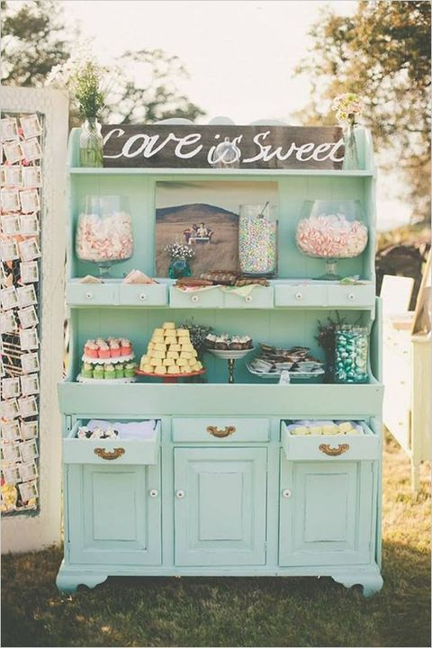 a beautiful vintage candy bar in mint green, with a chlkboard sign, candies in jars and other sweets in jars