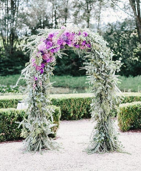 a beautiful wedding arch covered with eucalyptus and purple blooms is a very lovely and chic idea to rock