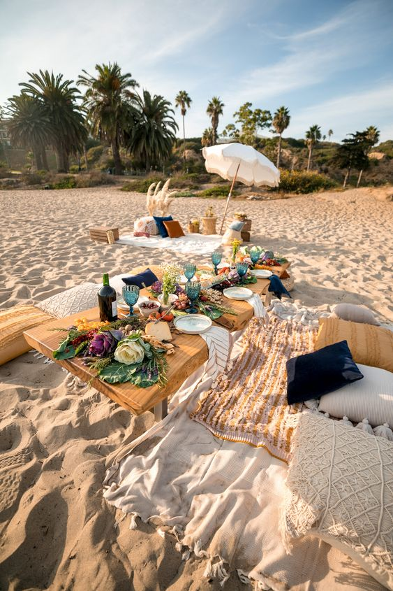 a boho beach picnic with boho rugs, pillows, candles, blue glasses, a vegetable table runner and a lounge zone with an umbrella