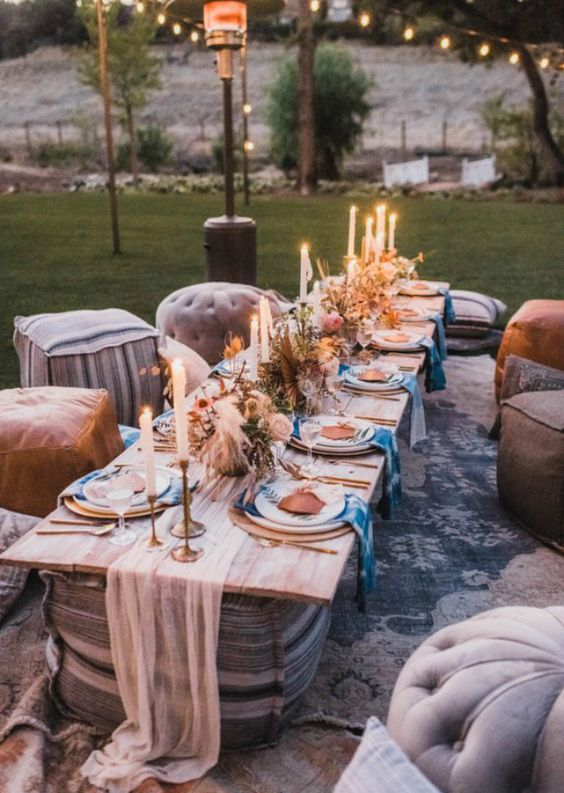 a boho chic picnic setting with candles, pampas grass, greenery and pink blooms, dip dyed napkins and leather ottomans