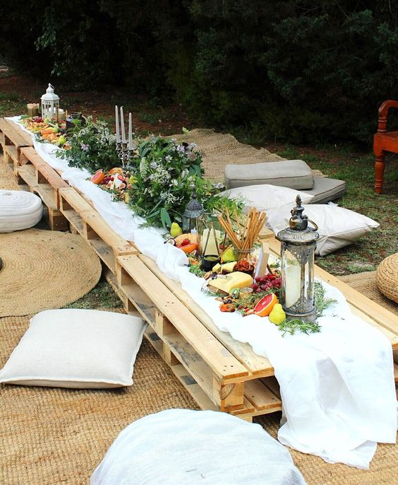 a boho picnic with a low table, with greenery, candle lanterns, neutral pillows and a vegetable and fruit table runner