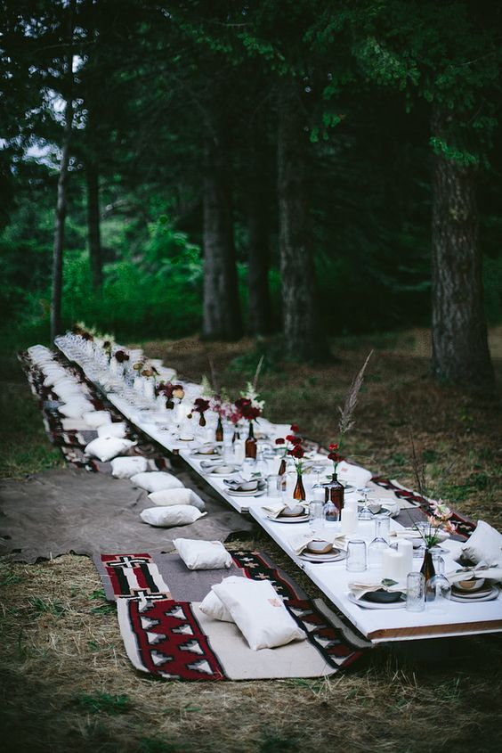 a boho woodland picnic with a low table, boho rugs, dark blooms, printed textiles and neutrals