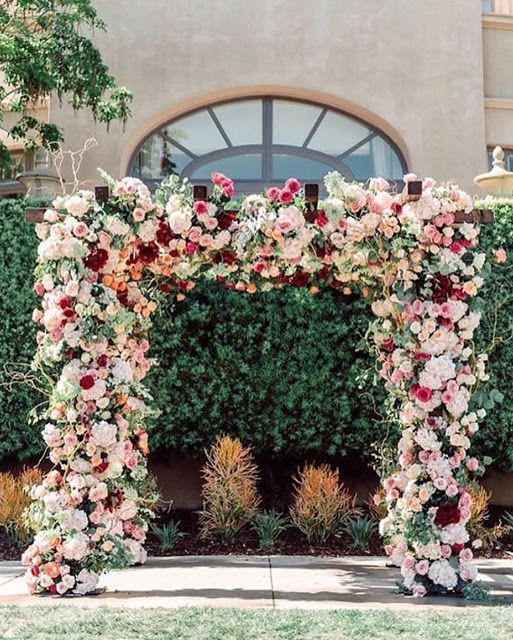 a bold and lush floral wedding arch with white, blush, light pink and burgundy blooms and greenery is amazing