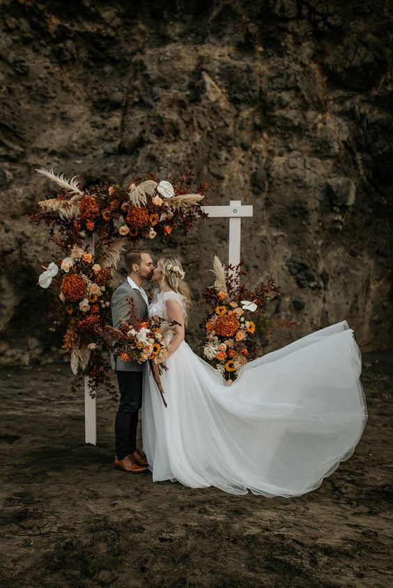 a bold boho wedding arch with orange, rust and white blooms, pampas grass and some dark foliage for a fall boho wedding