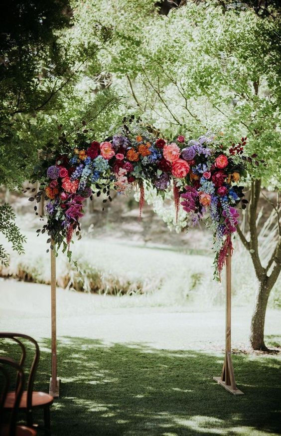 a bold jewel toned wedding arch with purple, blue, pink, burgundy and deep purple blooms and some foliage