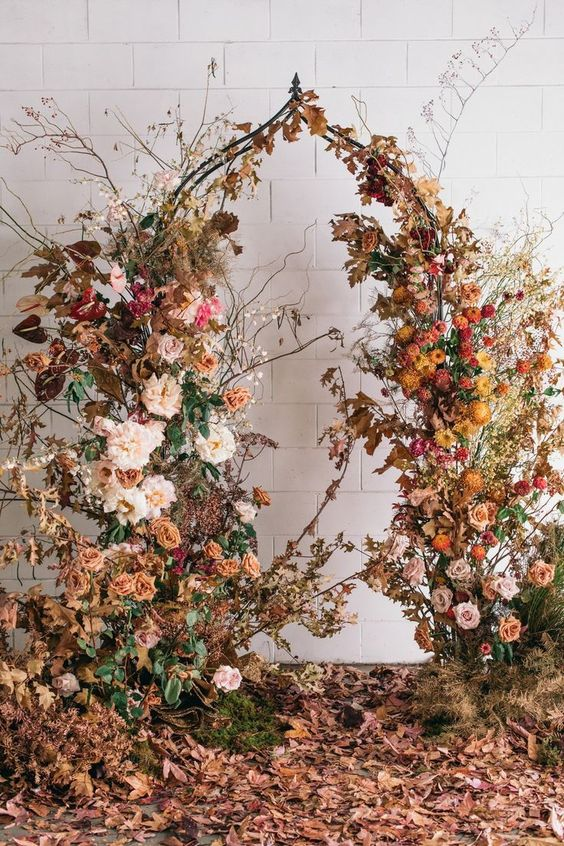 a breathtaking fall wedding arch covered with orange, yellow, blush and pink blooms, dried fall leaves and dried fall branches
