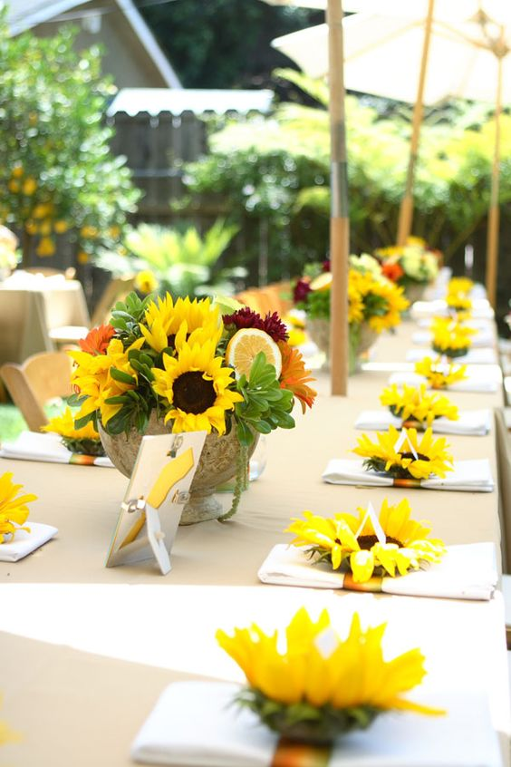a bright bbq rehearsal dinner table with a colorful sunflower and citrus centerpiece and sunflowers marking each napkin
