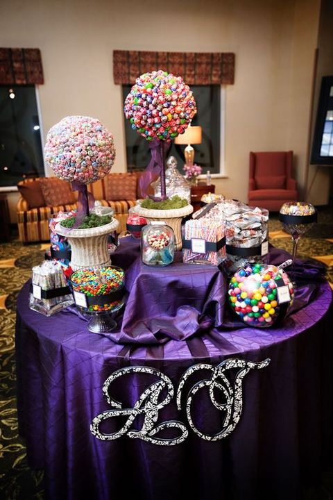 a bright candy bar with a purple tablecloth, monograms, colorful candies arranged in several ways