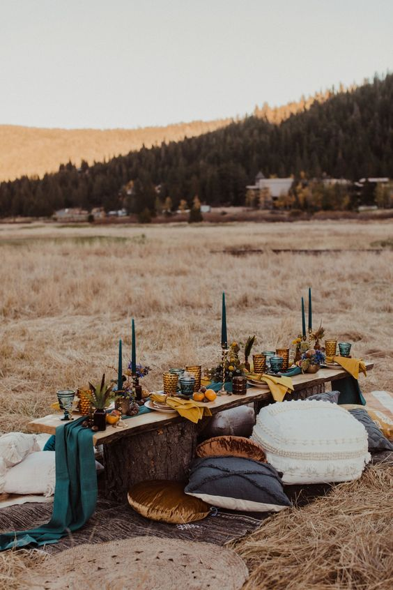 a bright fall boho picnic with a stump table, bright and printed pillows, teal candles and colorful napkins and textiles