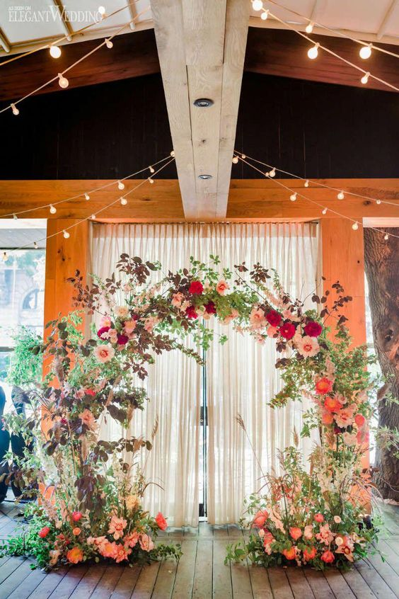 a bright floral wedding arch with coral, pink, red and orange blooms, greenery, dark foliage and pampas grass for a summer or fall boho wedding