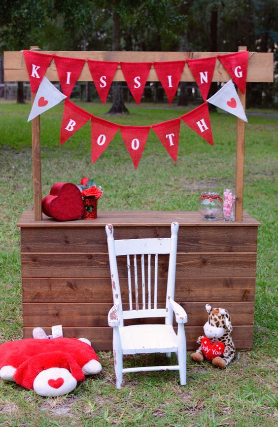 a bright kisisng booth of rich stained wood, with colorful banners, plush toys and red hearts for decor