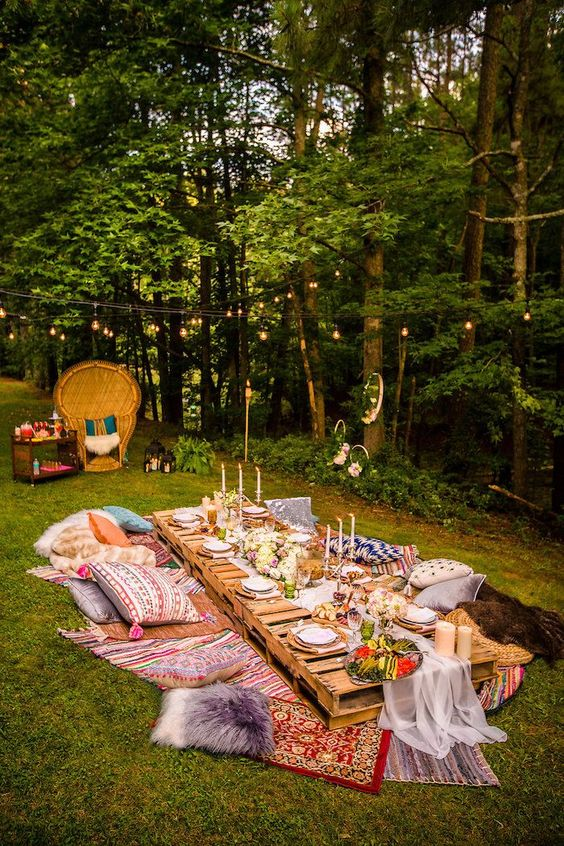 a bright summer picnic with a low table, boho rugs, pillows, candles and an airy runner plus string lights over the table