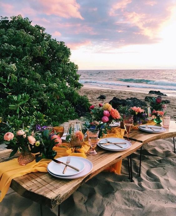 a bright tropical picnic setting with low tables, bright blooms, a yellow runner and candle lanterns for a rehearsal dinner