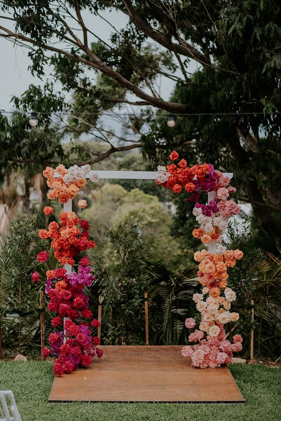 a bright wedding arch with a color block effect, with orange, red, hot pink, blush and white roses is wow