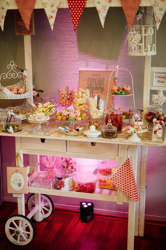 a candy bar with a white cart, bright banners, cool stands and jars and bowls looks very festive