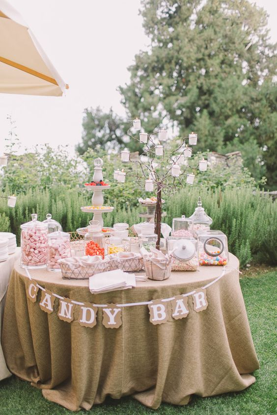 a candy table with pastel candies in jars, bowls and stands and a whimsy tree candle stand