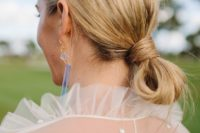a casual low knot updo with a messy top is a cool idea for a modern or minimalist bride