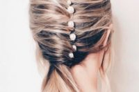 a catchy low ponytail with a twist and several pearl pins for a modern bride-to-be