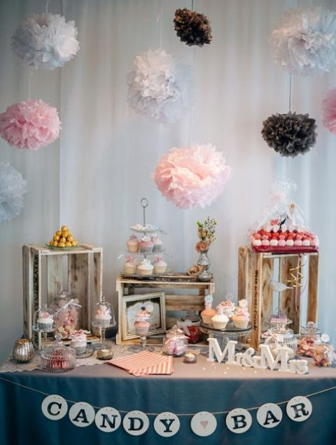 a chic candy bar with a grey tablecloth and a banner, paper popoms over the table and candies placed on crates and on stands