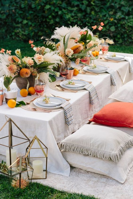 a chic garden rehearsal picnic with neutral and bright textiles, bright blooms, citrus, potted cacti and candle lanterns