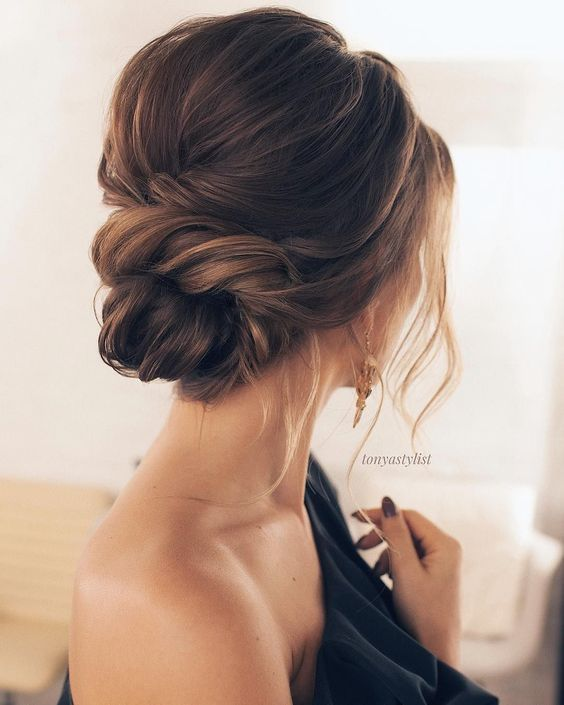 a chic twisted low bun with a small bump and some locks down for a timelessly romantic look